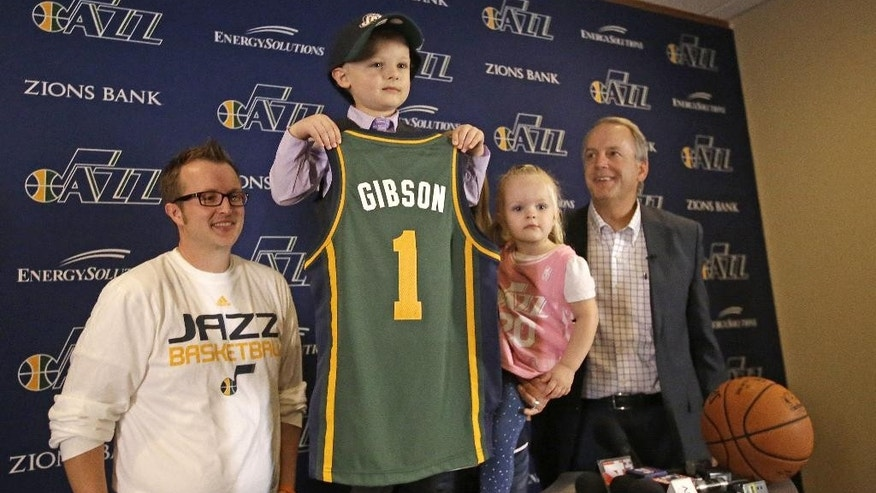 JP Gibson holds his jersey as Utah Jazz president Randy Rigby, right, his father Josh Gibson and sister Elie look on during a news conference Monday, Oct. 6, 2014, in Salt Lake City. The Utah Jazz signed the 5-year-old free agent guard to a one-day contract for a special scrimmage on Monday night. JP Gibson, who was diagnosed with acute lymphoblastic leukemia, signed his contract with Rigby before joining the team in uniform for the annual preseason intrasquad scrimmage at EnergySolutions Arena.  (AP Photo/Rick Bowmer)