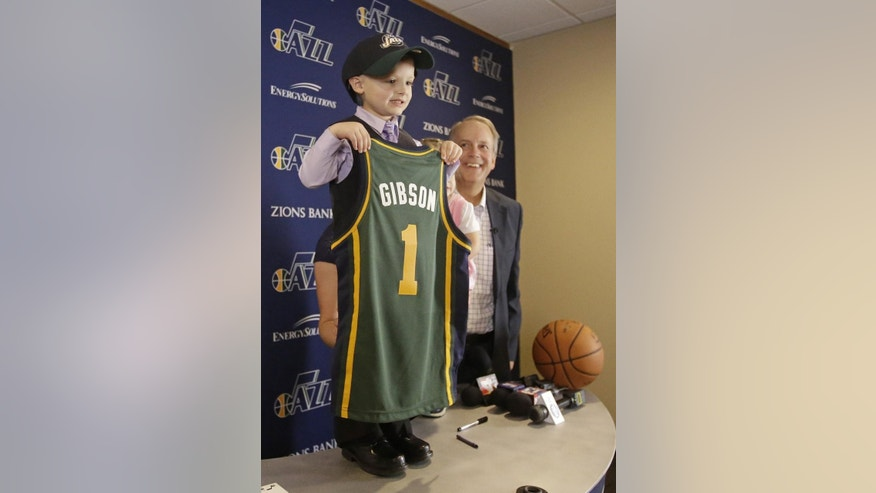 JP Gibson holds his jersey as Utah Jazz president Randy Rigby looks on during a news conference Monday, Oct. 6, 2014, in Salt Lake City. The Utah Jazz are signing a 5-year-old free agent guard to a one-day contract for a special scrimmage on Monday night. JP Gibson, who was diagnosed with acute lymphoblastic leukemia, signed his contract before joining the team in uniform for the annual preseason intrasquad scrimmage at EnergySolutions Arena.  (AP Photo/Rick Bowmer)
