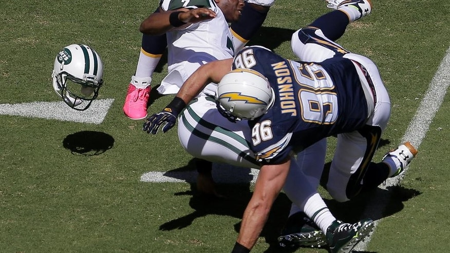 San Diego Chargers outside linebacker Jarret Johnson tackles New York Jets quarterback Geno Smith and knocks off his helmet during the first half of an NFL football game, Sunday, Oct. 5, 2014, in San Diego.  (AP Photo/Chris Carlson)