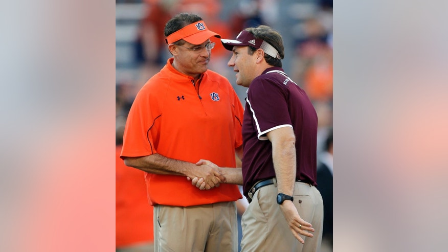 FILE - In this Sept. 14, 2013, file photo, Auburn coach Gus Malzahn, left, shakes hands with Mississippi State coach Dan Mullen prior to an NCAA college football game in Auburn, Ala. No. 3 Mississippi State has its highest ranking ever and now hosts possibly the biggest game in school history when No. 2 Auburn comes to town on Saturday, Oct. 11, 2014. (AP Photo/Dave Martin, File)