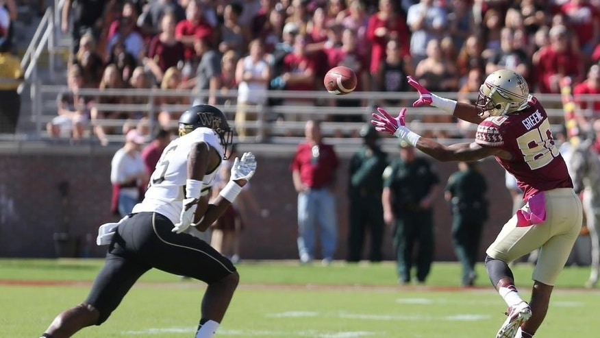Florida State's Rashad Greene makes a reception as Wake Forest's Thomas Brown rushes in to make the tackle in the second quarter of an NCAA college football game, Saturday Oct. 4, 2014 in Tallahassee, Fla. (AP Photo/Steve Cannon)