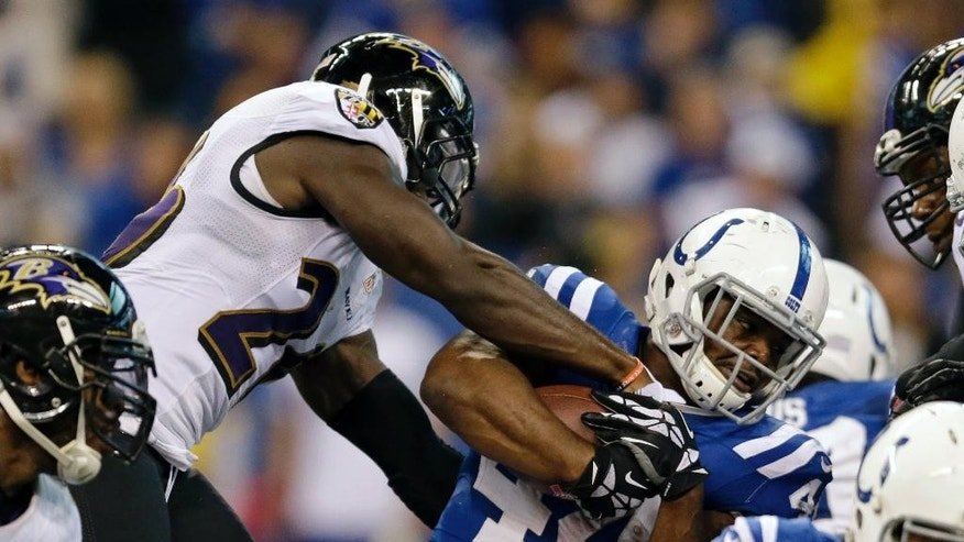 Baltimore Ravens strong safety Matt Elam, left, rips the ball away from Indianapolis Colts running back Ahmad Bradshaw (44) during the second half of an NFL football game in Indianapolis, Sunday, Oct. 5, 2014. The Colts defeated the Ravens 20-13. (AP Photo/Jeff Roberson)