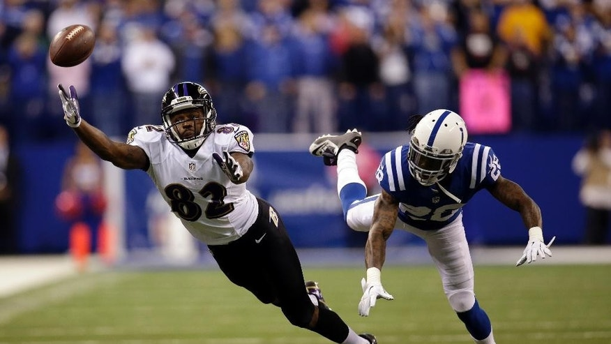 The ball falls out of reach of Baltimore Ravens wide receiver Torrey Smith, left, as he defended by Indianapolis Colts cornerback Greg Toler on a fourth down play in the final minute of an NFL football game in Indianapolis, Sunday, Oct. 5, 2014. The Colts defeated the Ravens 20-13. (AP Photo/AJ Mast)