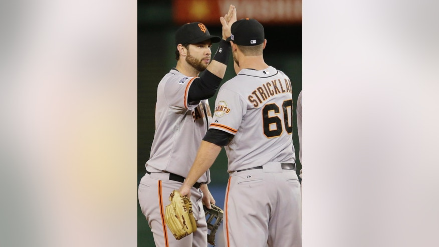 San Francisco Giants first baseman Brandon Belt (9) celebrates with relief pitcher Hunter Strickland (60) after Game 2 of baseball's NL Division Series against the Washington Nationals in Nationals Park, early Sunday, Oct. 5, 2014, in Washington. The Giants defeated the Nationals 2-1. (AP Photo/Patrick Semansky)