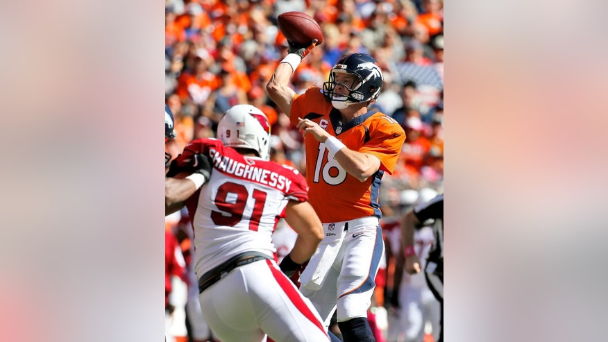 Denver Broncos quarterback Peyton Manning (18) throws under pressure from Arizona Cardinals outside linebacker Matt Shaughnessy (91) during the first half of an NFL football game, Sunday, Oct. 5, 2014, in Denver. (AP Photo/Jack Dempsey)