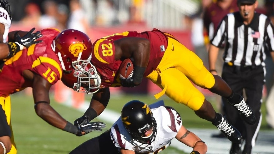 Arizona State defensive back Jordan Simone (38) tackles Southern California tight end Randall Telfer (82) as teammate wide receiver Nelson Agholor (15) looks on during the first half of an NCAA college football game, Saturday, Oct. 4, 2014, in Los Angeles. (AP Photo/Gus Ruelas)