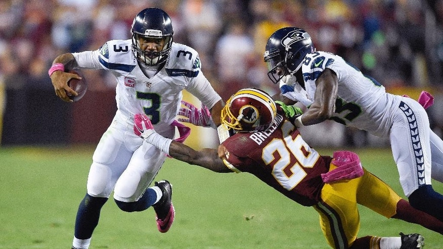 Seattle Seahawks quarterback Russell Wilson (3) escapes the grasp of Washington Redskins strong safety Bashaud Breeland (26) during the first half of an NFL football game in Landover, Md., Monday, Oct. 6, 2014. (AP Photo/Nick Wass)