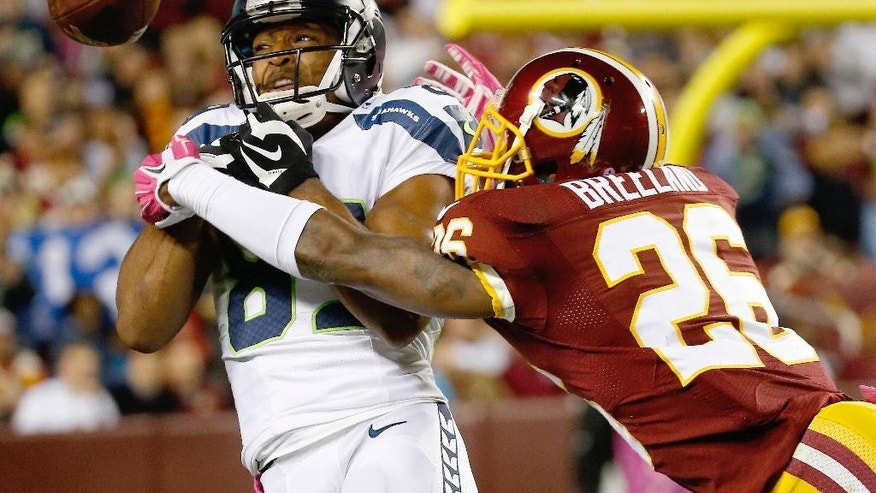 Washington Redskins strong safety Bashaud Breeland (26) breaks up a pass intended for Seattle Seahawks wide receiver Doug Baldwin (89) during the first half of an NFL football game in Landover, Md., Monday, Oct. 6, 2014. (AP Photo/Alex Brandon)