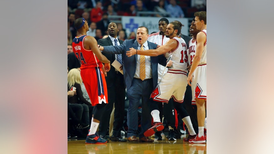 Chicago Bulls head coach Tom Thibodeau gets between Washington Wizards forward Paul Pierce (34) and Bulls center Joakim Noah (13) during a time-out during the first half of a pre-season NBA basketball game in Chicago, on Monday Oct. 6, 2014. (AP Photo/Jeff Haynes)
