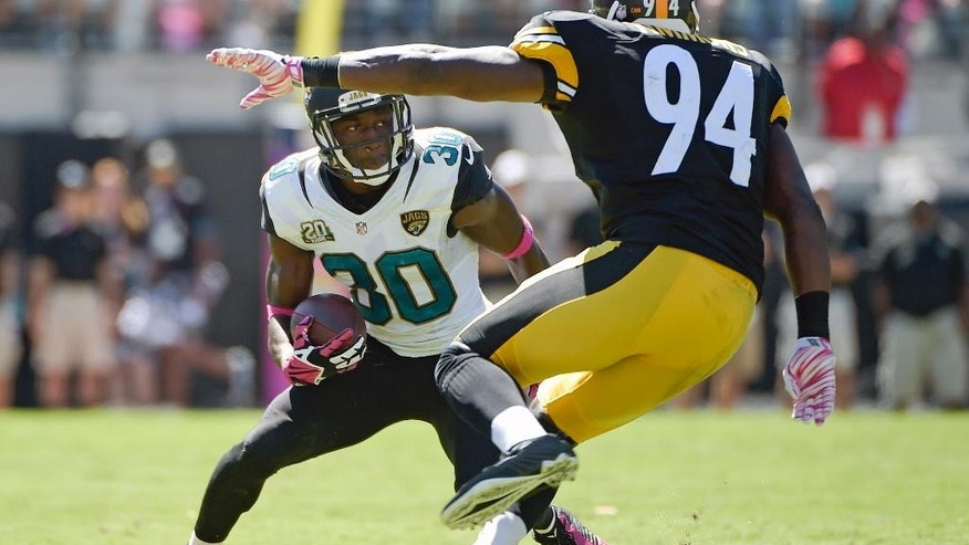 Jacksonville Jaguars running back Jordan Todman (30) looks for a way around Pittsburgh Steelers inside linebacker Lawrence Timmons (94) during the first half of an NFL football game in Jacksonville, Fla., Sunday, Oct. 5, 2014. (AP Photo/Phelan M. Ebenhack)