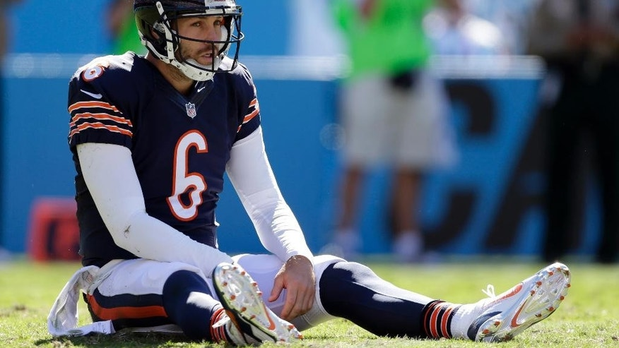 Chicago Bears' Jay Cutler (6) sits on the ground after being hit after a pass against the Carolina Panthers during the second half of an NFL football game in Charlotte, N.C., Sunday, Oct. 5, 2014. (AP Photo/Bob Leverone)