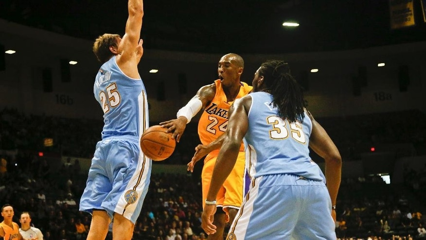 Los Angeles Lakers guard Kobe Bryant makes a no look pass around Denver Nuggets center Timofey Mozgov, left,  during the first half of an NBA preseason basketball game  Monday, Oct. 6, 2014, in San Diego. (AP Photo/Lenny Ignelzi