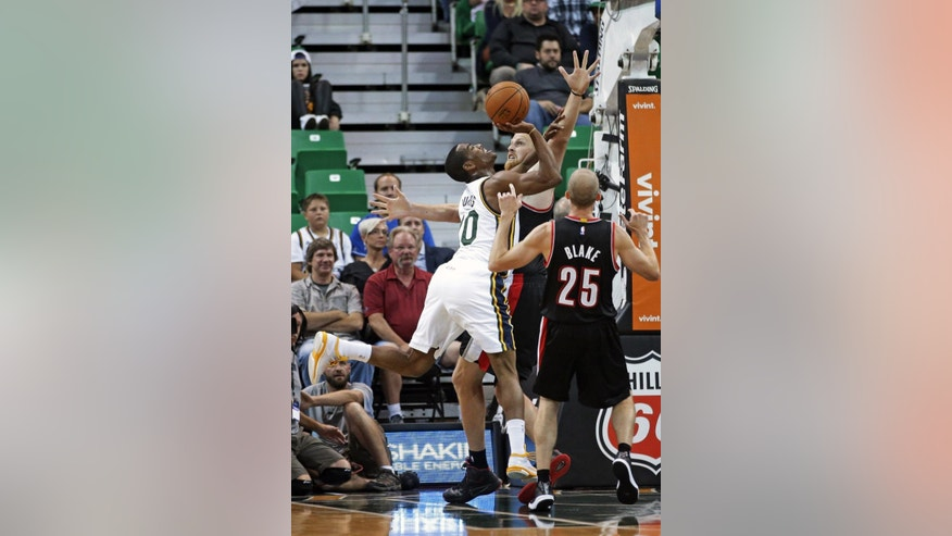 Utah Jazz's Alec Burks (10) shoots as Portland Trail Blazers' Chris Kaman, rear, defends while teammate Portland Trail Blazers' Steve Blake (25) looks on in the second quarter during an NBA preseason basketball game Tuesday, Oct. 7, 2014, in Salt Lake City. (AP Photo/Rick Bowmer)