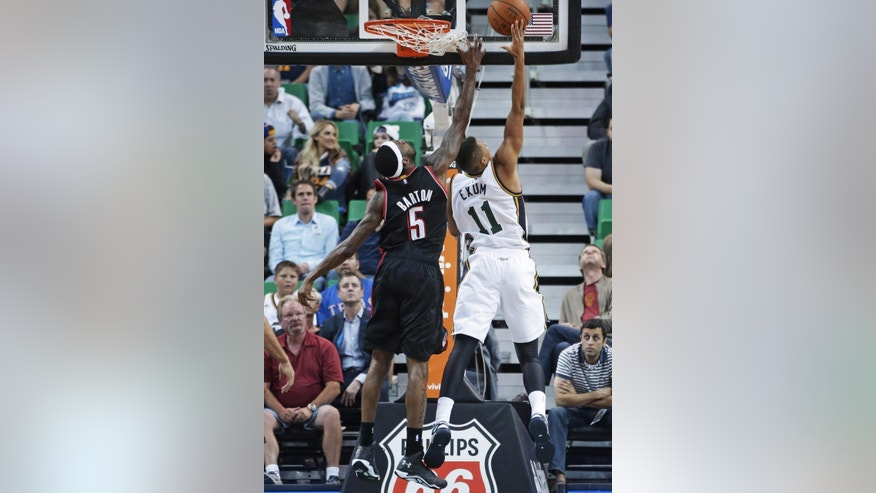 Utah Jazz's Dante Exum (11), of Australia, lays the ball up as Portland Trail Blazers' Will Barton (5) defends in the second quarter during an NBA preseason basketball game Tuesday, Oct. 7, 2014, in Salt Lake City. (AP Photo/Rick Bowmer)