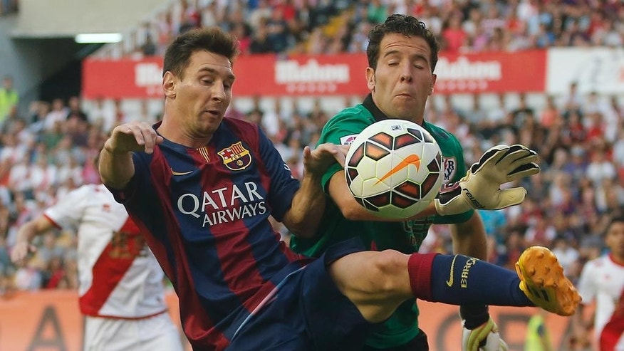 Barcelona's Lionel Messi, left, in action with  Rayo's goalkeeper Tono during a Spanish La Liga soccer match between Rayo Vallecano and FC Barcelona at the Vallecas stadium in Madrid, Spain, Saturday, Oct. 4, 2014. (AP Photo/Andres Kudacki)