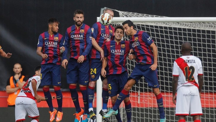 Barcelona's players try to stop the ball after a free kick during a Spanish La Liga soccer match between Rayo Vallecano and FC Barcelona at the Vallecas stadium in Madrid, Spain, Saturday, Oct. 4, 2014. (AP Photo/Andres Kudacki)