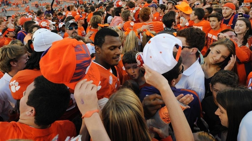 Clemson quarterback Deshaun Watson, center, signs a fan's cast after an NCAA college football game against North Carolina State, Saturday, Oct. 4, 2014, in Clemson, S.C. Clemson won 41-0. (AP Photo/Rainier Ehrhardt)