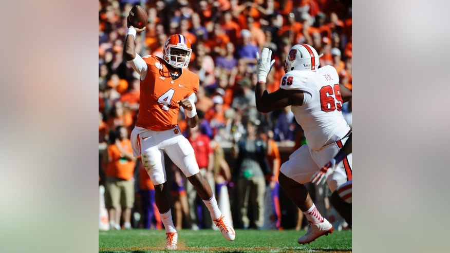 Clemson quarterback Deshaun Watson (4) throws as North Carolina State defensive tackle Thomas Teal (69) defends during the first half of an NCAA college football game, Saturday, Oct. 4, 2014, in Clemson, S.C. (AP Photo/Rainier Ehrhardt)