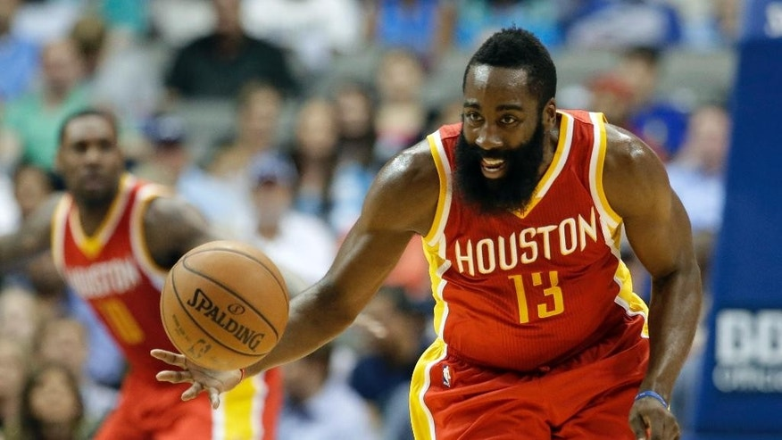 Houston Rockets' James Harden (13) comes away with a steal against the Dallas Mavericks in the first half of a preseason NBA basketball game, Tuesday, Oct. 7, 2014, in Dallas. (AP Photo/Tony Gutierrez)