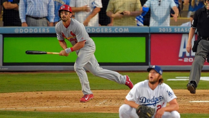 St. Louis Cardinals' Matt Carpenter, left, watches his a three-run double as Los Angeles Dodgers starting pitcher Clayton Kershaw, right, crouches on the mound in the seventh inning of Game 1 of baseball's NL Division Series in Los Angeles, Friday, Oct. 3, 2014. (AP Photo/Mark J. Terrill)