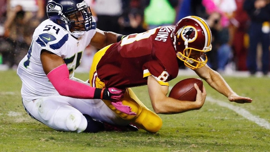 Washington Redskins quarterback Kirk Cousins (8) is sacked by Seattle Seahawks middle linebacker Bobby Wagner (54) during the second half of an NFL football game in Landover, Md., Monday, Oct. 6, 2014. (AP Photo/Alex Brandon)