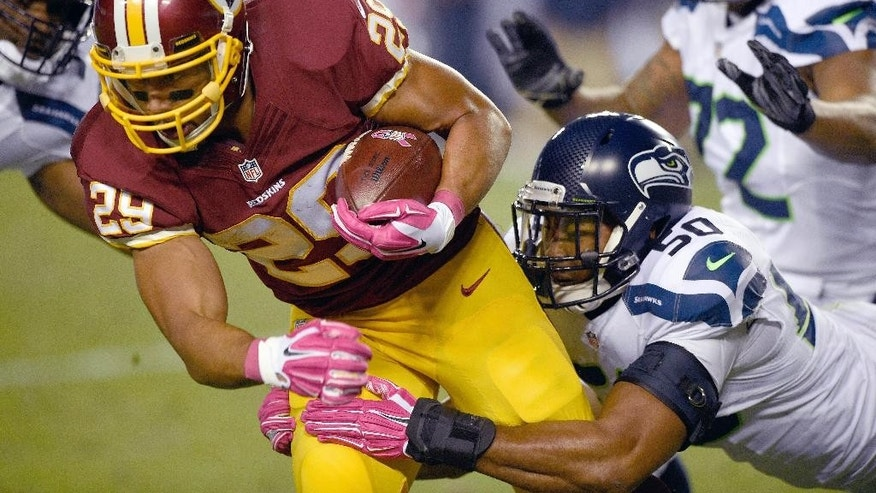 Washington Redskins running back Roy Helu (29) is hauled o the turf by Seattle Seahawks outside linebacker K.J. Wright (50) during the first half of an NFL football game in Landover, Md., Monday, Oct. 6, 2014. (AP Photo/Nick Wass)
