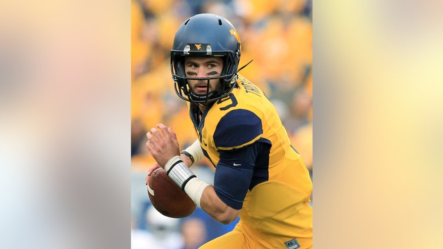 West Virginia quarterback Clint Trickett (9) rolls out of the pocket during the first quarter of an NCAA college football game against Kansas in Morgantown, W.Va., Saturday, Oct. 4, 2014. (AP Photo/Chris Jackson)