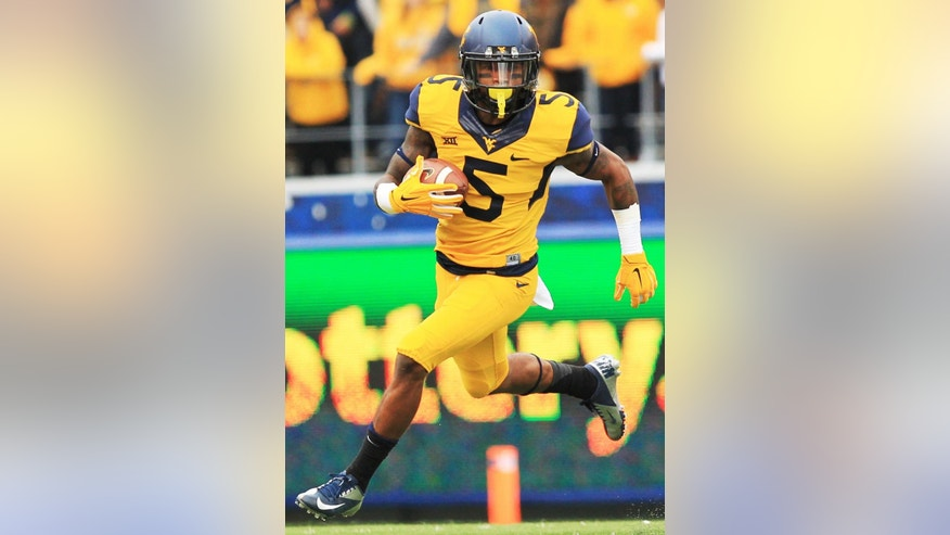 West Virginia's Mario Alford (5) carries the ball during the second quarter of an NCAA college football game against Kansas in Morgantown, W.Va., Saturday, Oct. 4, 2014. West Virginia won 33-14. (AP Photo/Chris Jackson)