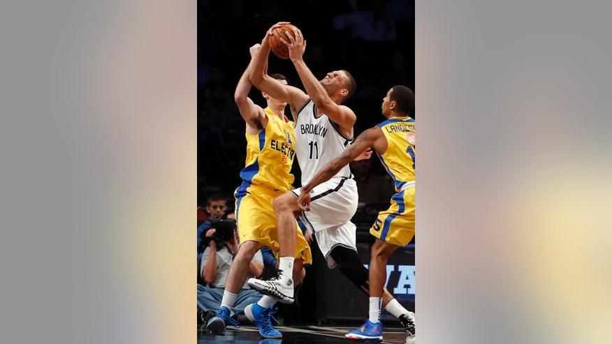 Brooklyn Nets' Brook Lopez (11) drives between a double team from Maccabi Tel Aviv's Jake Cohen, left, and Sylven Landesberg, right, during the first quarter of an NBA preseason basketball game Tuesday, Oct. 7, 2014, in New York. (AP Photo/Jason DeCrow)