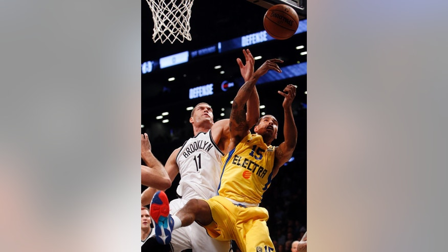 Brooklyn Nets' Brook Lopez (11) battles for a rebound against Maccabi Tel Aviv's Sylven Landesberg (15) during the first quarter of an NBA preseason basketball game Tuesday, Oct. 7, 2014, in New York. (AP Photo/Jason DeCrow)