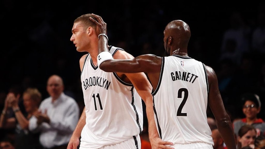 Brooklyn Nets' Brook Lopez (11) and Kevin Garnett (2) react as they head to the bench at the end of the first quarter during an NBA preseason basketball game against the Maccabi Tel Aviv Tuesday, Oct. 7, 2014, in New York. (AP Photo/Jason DeCrow)