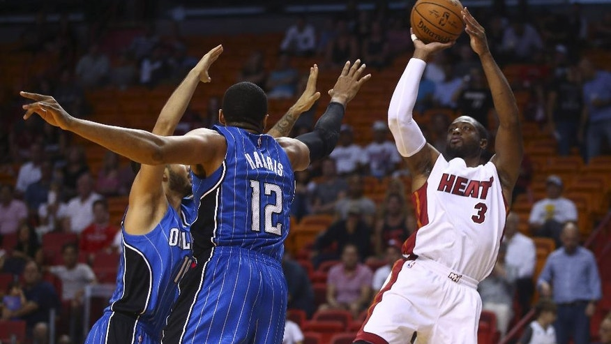 Orlando Magic players Evan Fournier (10) and Tobias Harris (12) try to block Miami Heat's Dwyane Wade (3) from taking a two point shot during the first half of  a NBA basketball game in Miami, Oct. 7, 2014. (AP Photo/J Pat Carter)