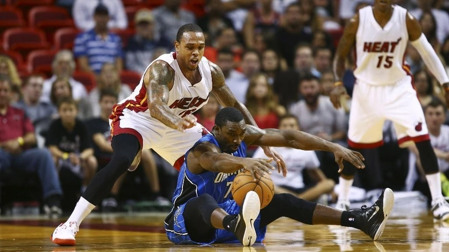 Miami Heat's Shannon Brown (26) tries to steal the ball from Orlando Magic's Ben Gordon (7) during the first half of  a NBA basketball game in Miami, Oct. 7, 2014. (AP Photo/J Pat Carter)