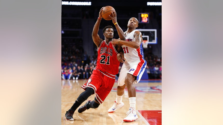 Chicago Bulls guard Jimmy Butler (21) drives on Detroit Pistons forward Caron Butler (31) in the first half of a preseason NBA basketball game in Auburn Hills, Mich., Tuesday, Oct. 7, 2014. (AP Photo/Paul Sancya)