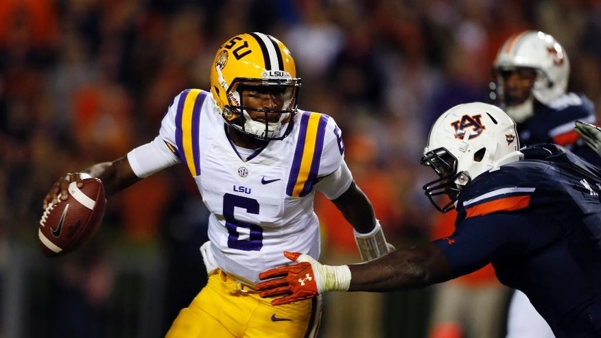 LSU quarterback Brandon Harris (6) scrambles away form Auburn defensive lineman Montravius Adams during the second half of an NCAA college football game Saturday, Oct. 4, 2014, in Auburn, Ala. (AP Photo/Butch Dill)