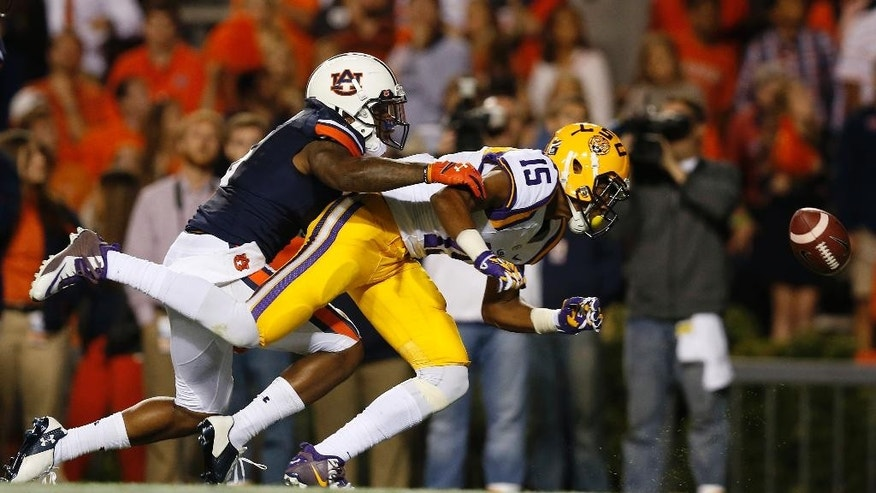 LSU wide receiver Malachi Dupre (15) reaches for a pass against Auburn defensive back Jonathon Mincy (6) during the second half of an NCAA college football game Saturday, Oct. 4, 2014, in Auburn, Ala. The pass fell incomplete. (AP Photo/Brynn Anderson)