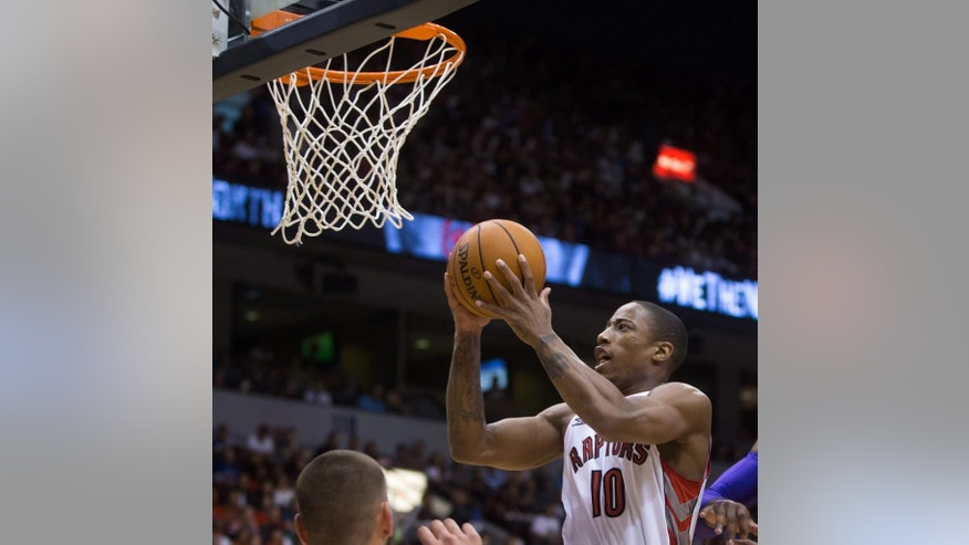 Toronto Raptors' DeMar DeRozan scores against the Sacramento Kings during the first half of a pre-season NBA basketball game in Vancouver, British Columbia, on Sunday Oct. 5, 2014. (AP Photo/The Canadian Press, Darryl Dyck)