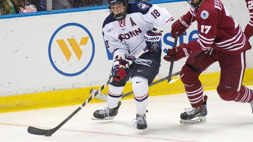 In this Dec. 30, 2013 photo released by the University of Connecticut, forward Trevor Gerling (18) carries the puck past University of Massachusetts defenseman Brennan Baxandall (17) in Hartford, Conn. The Huskies open the 2014-15 season in Division 1-AA, the newest member of Hockey East. (AP Photo/University of Connecticut, Stephen Slade)