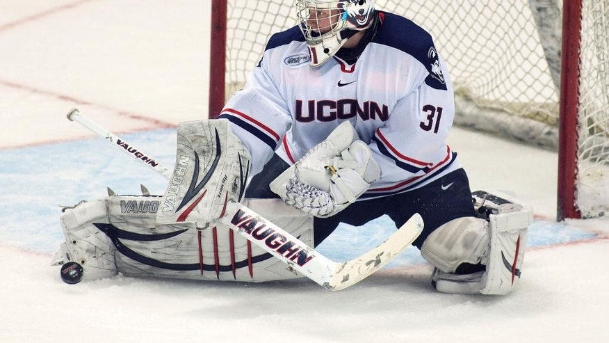 In this Dec. 30, 2013 photo released by the University of Connecticut, goalie Rob Nichols turns away a shot during a game against the University of Massachusetts in Hartford, Conn. The Huskies open the 2014-15 season in Division 1-AA, the newest member of Hockey East. (AP Photo/University of Connecticut, Stephen Slade)