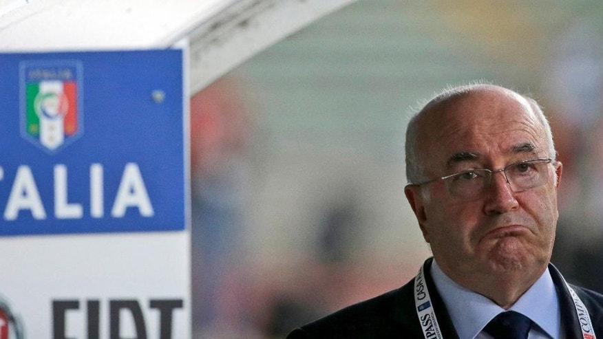In this photo taken on Thursday, Sept. 4, 2014, Paolo Tavecchio walks on the pitch prior to a friendly soccer match between Italy and The Netherlands in Bari, Italy. UEFA has banned Italian soccer federation president Carlo Tavecchio for six months following a racist comment during his electoral campaign. Tavecchio, a long-standing executive in Italian football, was elected president in August despite causing a stir over a reference to bananas when discussing the presence of foreign players in Italy. (AP Photo/Gregorio Borgia)