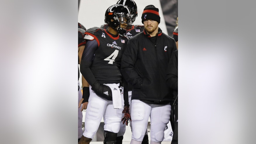 Cincinnati quarterback Munchie Legaux (4) talks with quarterback Gunner Kiel during the second half of an NCAA college football game against Memphis, Saturday, Oct. 4, 2014, in Cincinnati. Legaux replaced Kiel after Kiel suffered a chest injury on the final play of the first half. (AP Photo/Al Behrman)