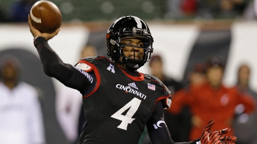 Cincinnati quarterback Munchie Legaux passes against Memphis in the second half of an NCAA college football game, Saturday, Oct. 4, 2014, in Cincinnati. Legaux replaced starting quarterback Gunner Kiel who suffered a chest injury on the final play of the first half. (AP Photo/Al Behrman)