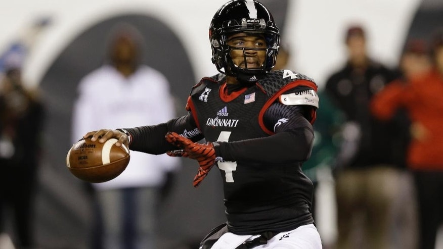 FILE - In this Oct. 4, 2014, file photo, Cincinnati quarterback Munchie Legaux (4) passes against Memphis in the second half of an NCAA college football game in Cincinnati. A year after his gruesome knee injury, Legaux is getting ready to be Cincinnati's starting quarterback again.(AP Photo/Al Behrman, File)