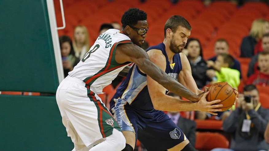 Milwaukee Bucks center Larry Sanders (8) knocks the ball out of the hands of Memphis Grizzlies center Marc Gasol during the first half of an NBA preseason basketball game Wednesday, Oct. 8, 2014, in Green Bay, Wis. (AP Photo/Matt Ludtke)