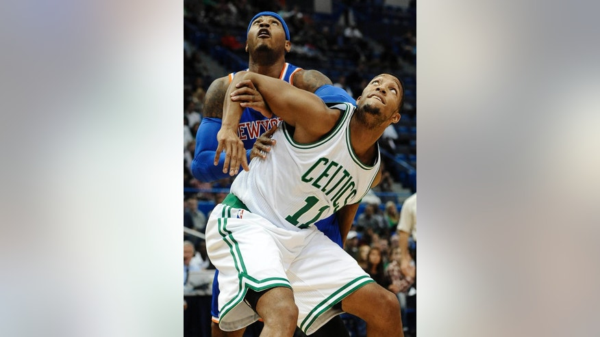 New York Knicks forward Carmelo Anthony and Boston Celtics guard Evan Turner (11), look for a rebound during the first during the first quarter of a preseason NBA basketball game , Wednesday, Oct. 8, 2014, in Hartford, Conn. (AP Photo/Jessica Hill)