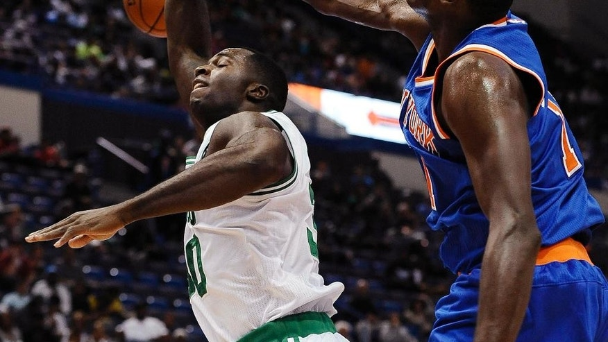 New York Knicks center Samuel Dalembert, right, blocks a shot attempt by Boston Celtics forward Brandon Bass during the second quarter of a preseason NBA basketball game , Wednesday, Oct. 8, 2014, in Hartford, Conn. (AP Photo/Jessica Hill)
