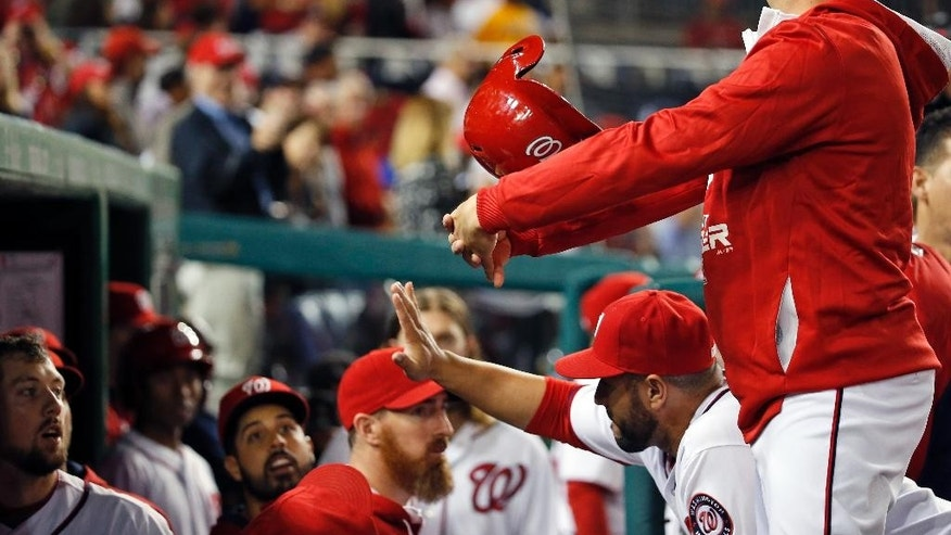 FILE - In this Sept. 26, 2014, file photo, Washington Nationals' Asdrubal Cabrera holds his arms like a basket as the helmet of Steven Souza is tossed through, in celebration after Souza's solo home run during the third inning of the second baseball game of a doubleheader at Nationals Park. Used to be that a major leaguer would homer and be greeted in the dugout with high-fives and handshakes.  (AP Photo/Alex Brandon)