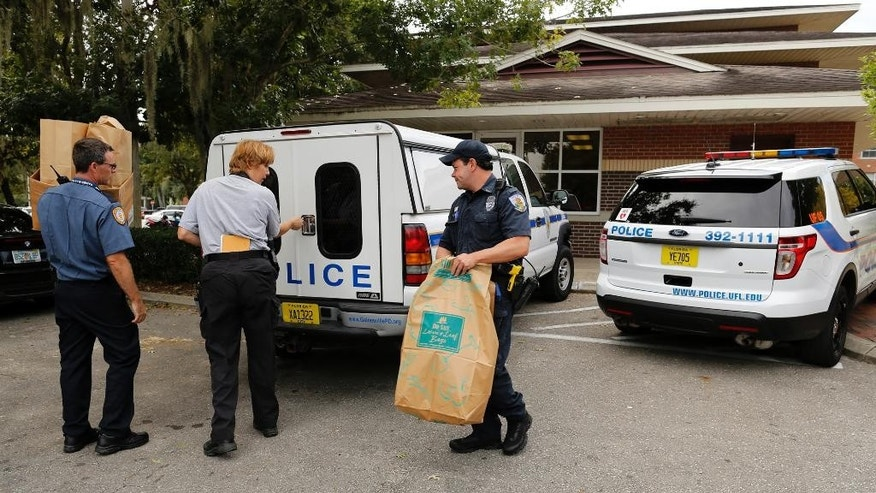 University of Florida Police and Gainesville Police leave the Springs residence hall on the UF campus with bags of evidence Monday, Oct. 6, 2014. Gainesville Police announced that it is assisting Uunivserity police in the collection of forensic evidence in the investigation of Florida quarterback Treon Harris, who is accused of sexual assault.   (AP Photo/The Gainesville Sun, )  THE INDEPENDENT FLORIDA ALLIGATOR OUT