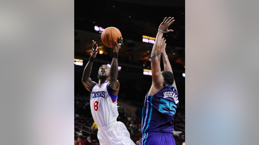 Philadelphia 76ers' Tony Wroten (8) drives to the basket and takes a shot as Charlotte Hornets' Al Jefferson defends during the first half of a preseason NBA basketball game in Philadelphia, Wednesday, Oct. 8, 2014. (AP Photo/Michael Perez)