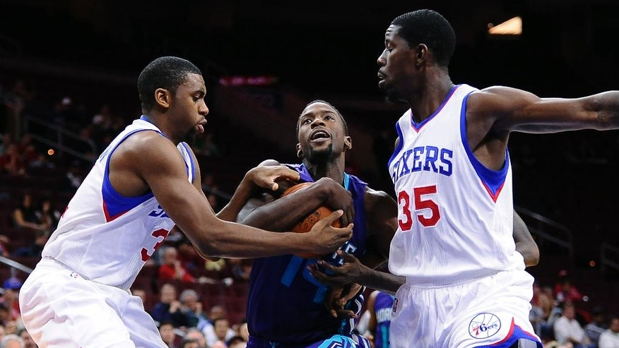 Charlotte Hornets' Michael Kidd-Gilchrist, center, drives past Philadelphia 76ers' Henry Sims (35) and Hollis Thompson during the first half of a preseason NBA basketball game in Philadelphia, Wednesday, Oct. 8, 2014. (AP Photo/Michael Perez)